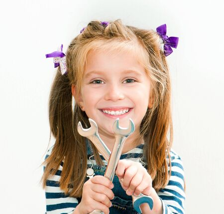 forkwrench: little smiling girl with a chrome spanners Stock Photo