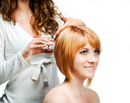 barbershop: Young woman barber makes hairstyle for a girl isolated on white background