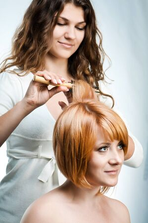 combing hair: Young fashion woman hairdresser makes hairstyle for a girl isolated on white background Stock Photo
