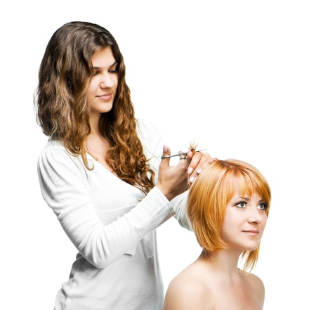Young nice woman hairdresser makes hairstyle for a girl isolated on white background photo