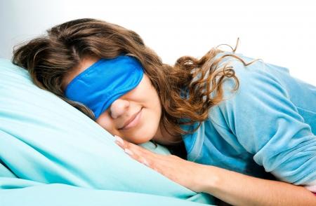 Beautiful sleeping young woman in sleep eye mask on blue furnishing photo