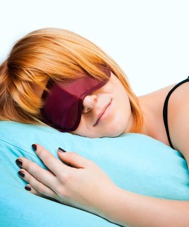 eye mask: Sleeping young woman in sleep eye mask on blue furnishing