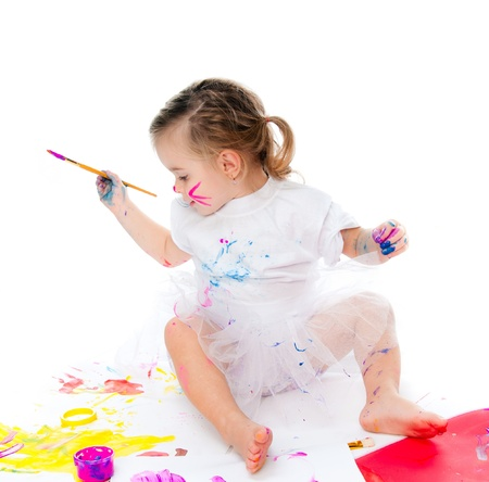 painter girl: cute little girl with a brush and paints on a white