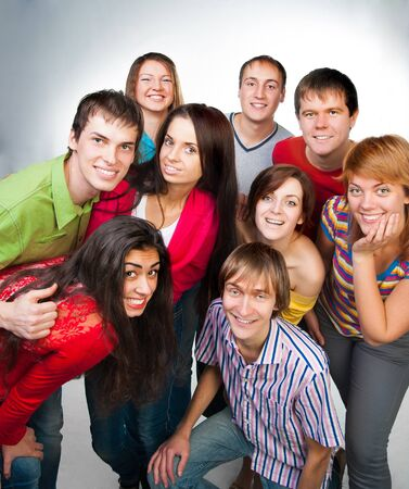 group of casual happy people smiling and standing over a light background photo
