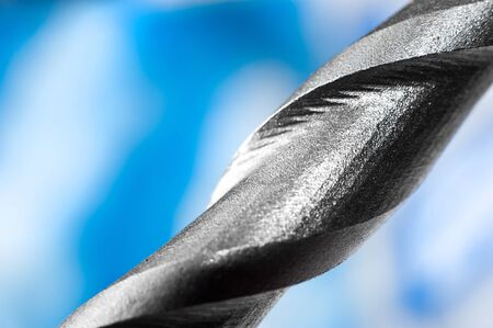 perforate: macro closeup of a metal drilling bit on blue background