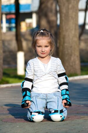 Little girl in roller skates at a park photo