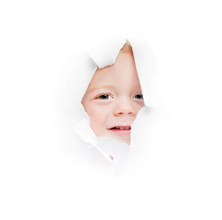 furtively: child looks in a hole in a sheet of a paper Stock Photo