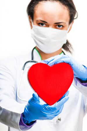 Doctor holding red heart symbol on white background photo