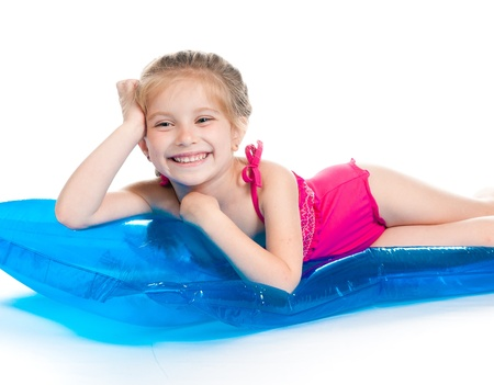 enfant maillot de bain: mignonne petite fille dans un maillot de bain sur un matelas gonflable Banque d'images