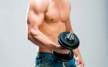 heavy lifting: Torso of muscular man with weights on a gray background