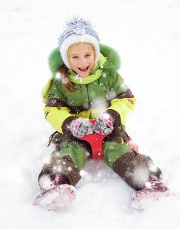 Happy child on sledge in winter