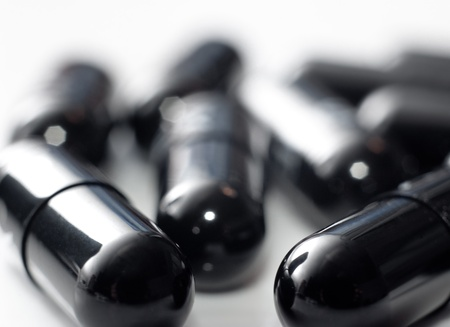 Macro of black capsules on white background photo