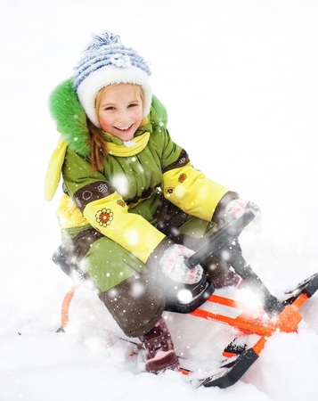 Smiling Happy litte girl with children s snowmobile