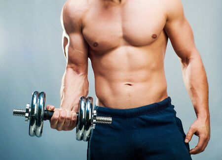 back muscles: attractive athletic male torso with dumbbells