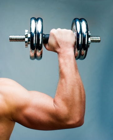 Arm attractive athletic man with dumbbells photo