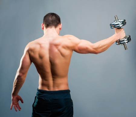 back muscles: Rear view of a young male bodybuilder doing heavy weight exercise with dumbbells against gray backg