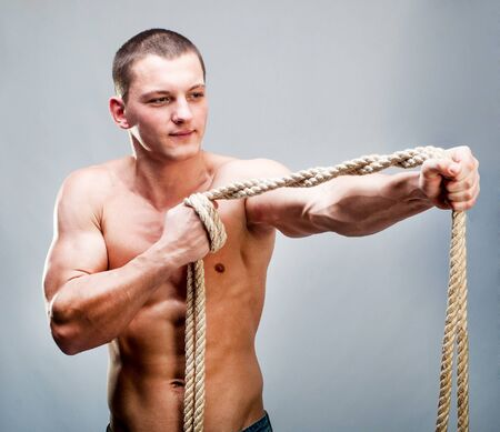 Attractive muscular man rope breaks photo
