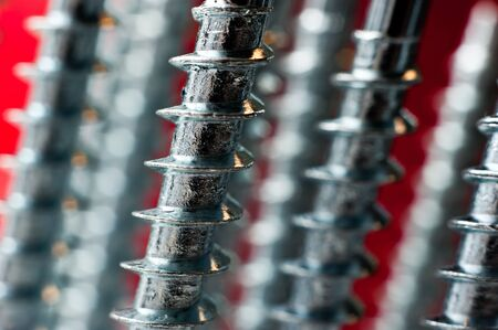 chrome screw on a blur red background photo