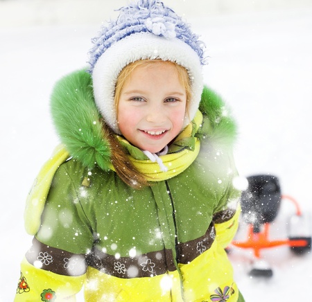 children's: Portrait of Happy litte girl with children s snowmobile