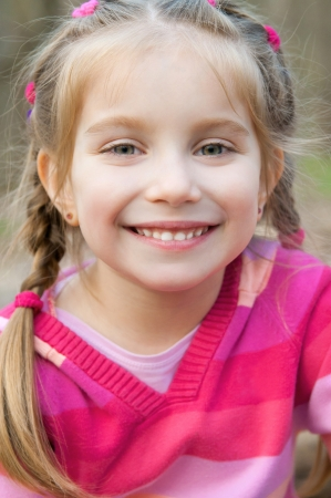 cute little girl smiling: cute little girl smiling in a park close-up