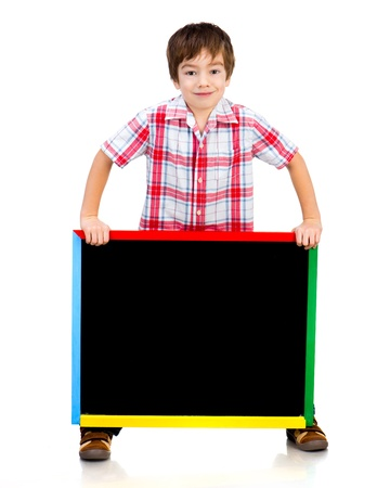 niños con pancarta: Muchacho sonriente sosteniendo una pizarra sobre fondo blanco Foto de archivo
