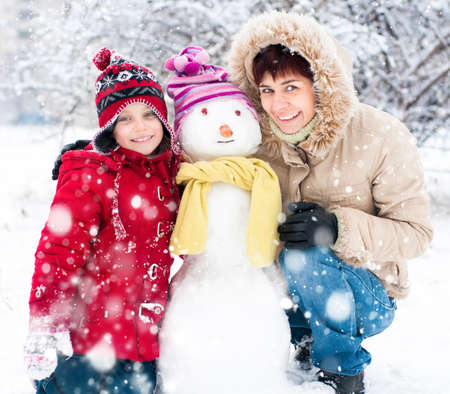 atcamera: Happy mother and daughter with snowman winter portrait Stock Photo
