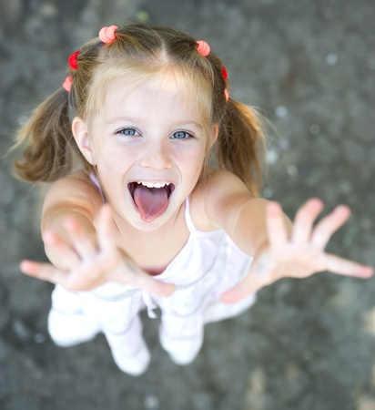 big eyes: Portrait of smiling pretty little girl with hands up