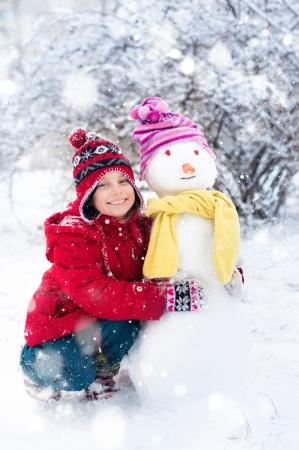 Kız kış saati dışında bir kardan adam yapar Stock Photo