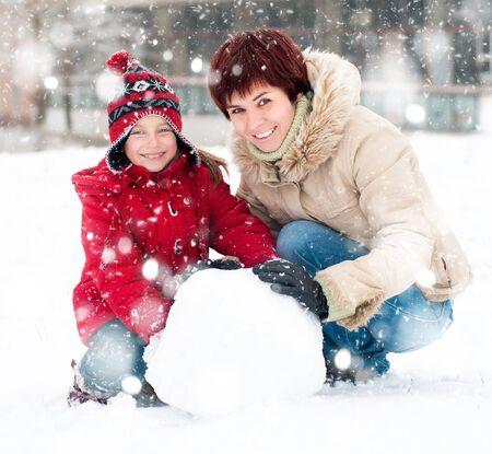 atcamera: Happy family with snowman winter portrait Stock Photo