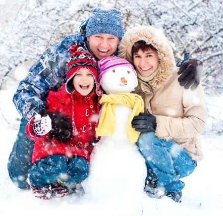 freeze: Happy smiling family with snowman winter portrait