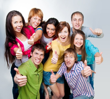 group of casual happy people smiling and shows fingers at the camera photo