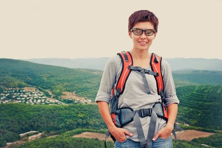 Portrait of smiling girl in glasses on a mountain hill photo