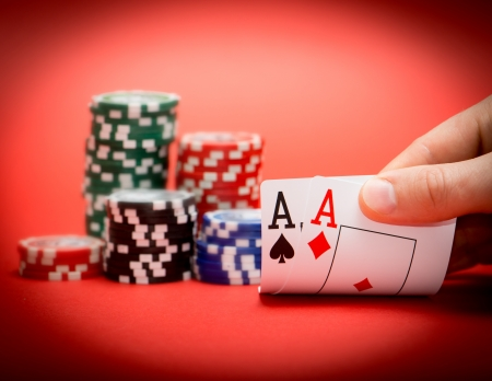 wager: Stack of chips and two aces on a red poker table Stock Photo