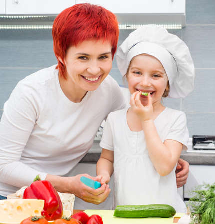Mother and cute daughter in the kitchen with vegetables photo