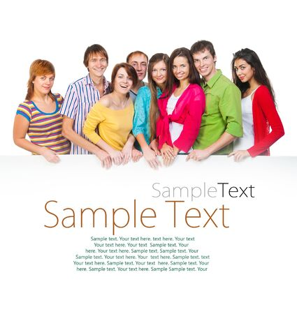 Happy young group of people standing together and holding a blank with sample text photo