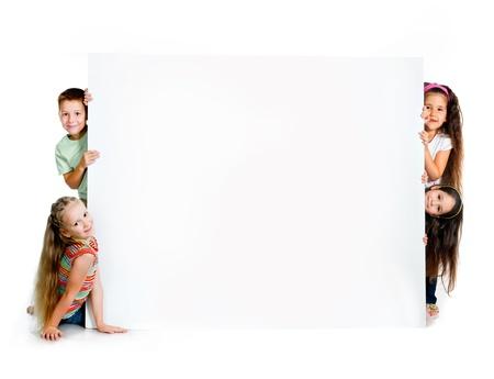 ni�os sosteniendo un cartel: ni�os al lado de un blanco en blanco para el texto o la imagen Foto de archivo