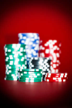 stacks of colour chips on red poker table photo