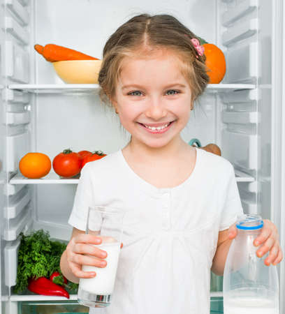 refrigerator with food: little girl with milk against a refrigerator with food Stock Photo