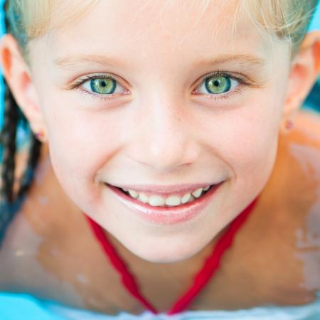 teen girl bikini: Closeup face of Smiling little girl in swimming pool