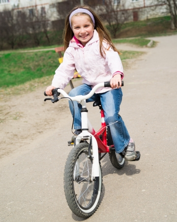 Cute smiling little girl with bicycle on road photo