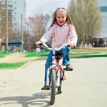 riding bike: Bambina su una bicicletta nel parco di estate