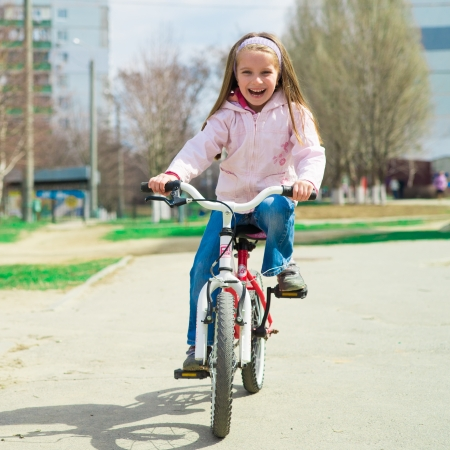 riding helmet: Ni�a en una bicicleta en el parque de verano