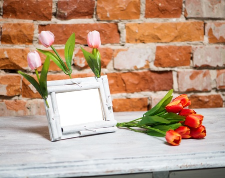 photo frame with bouquet of tulips on a white table photo