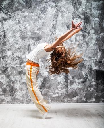 estilo urbano: dancind chica sobre un fondo gris del grunge