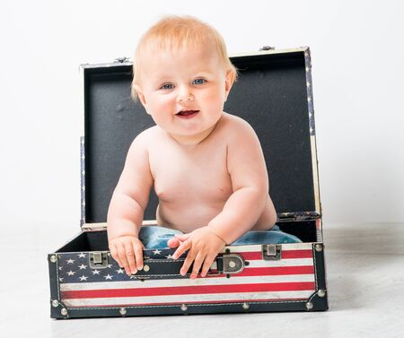 cute baby in a suitcase with American flag photo