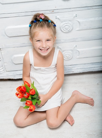 Cute little girl with a bouquet of flowers sitting on the floor photo