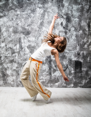 break dance: dancind girl on a gray grunge background