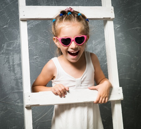 niño escalando: Niña sonriente con gafas de sol en las escaleras blancas