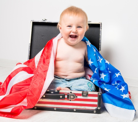 smiling cute baby in a suitcase with American flag photo