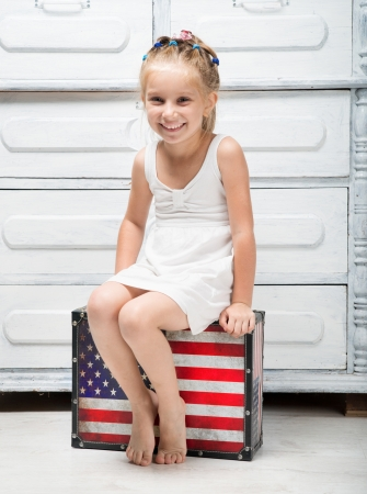 niña: niña con una maleta en colores de la bandera americana Foto de archivo